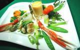 Légumes primeurs, huile de carapaces, langoustine royale, joues de raies caramélisées et jaune doux en écume de rouille